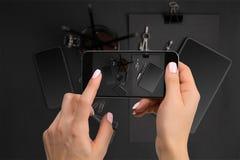 Cancelleria nera di fucilazione sulla macchina fotografica del ` s del telefono Cancelleria su fondo nero Fotografia Stock