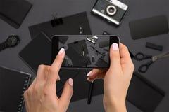 Cancelleria nera di fucilazione sulla macchina fotografica del ` s del telefono Cancelleria su fondo nero Immagine Stock