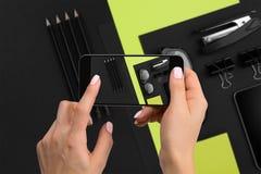 Cancelleria nera di fucilazione sulla macchina fotografica del ` s del telefono Cancelleria su fondo nero verde Fotografie Stock