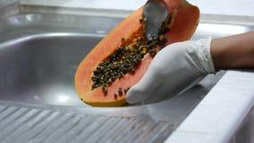 Cancelli i semi della papaia dopo buccia al lavandino stock footage