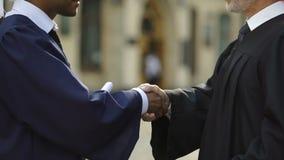 Cancelliere dell'università che dà diploma al dottorando che stringe mano, fine su video d archivio