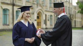 Cancelliere dell'università che dà diploma allo studente, stringente mano, inizio archivi video