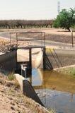 Cancello del canale di irrigazione con i frutteti nella priorità bassa Immagini Stock