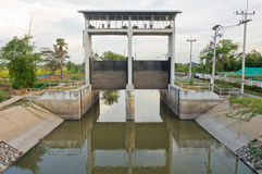 Cancello della diga e dell'acqua in un canale di irrigazione fotografia stock