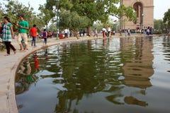 Cancello Nuova Delhi dell'India della gente con la riflessione dell'acqua Immagine Stock