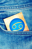 Cancer. Astrology card with zodiac sign of cancer in a blue jeans pocket royalty free stock photo