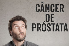 Cancer de prostata, Portuguese text for Prostate Cancer man writ. Cancer de prostata, Portuguese text for Prostate Cancer, , sceptical man looking at text grunge royalty free stock photo