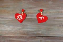 Cancer et Bélier signes du zodiaque et de coeur Backgrou en bois Photos stock