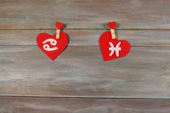 Cancer and fish. signs of the zodiac and heart. wooden backgroun stock image