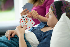 Cancer girl playing cards. In hospital bed Royalty Free Stock Photography