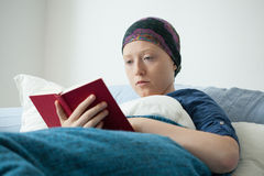 Cancer girl reading book Stock Image