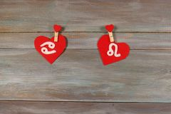 Cancer and a lion. signs of the zodiac and heart. wooden backgro. Und. card. Love. unusual handwork stock image