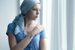 Cancer patient holding arm. Cancer patient holding her arm while looking out the window Royalty Free Stock Photo