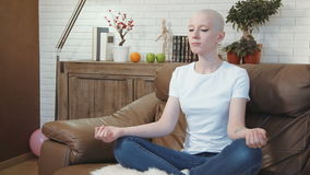 Cancer patient woman sits on a sofa and meditates