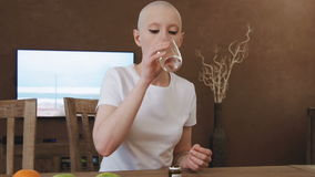 Cancer patient woman sits at the table and takes medicine pills