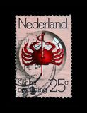 Cancer Research Fund, pierced red crab under lens, circa 1974,. NETHERLANDS - CIRCA 1974: stamp printed in Netherlands shows pierced red crab under lens Royalty Free Stock Photos