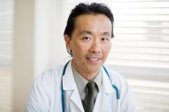 Cancer Specialist Smiling In Hospital. Portrait of Asian male cancer specialist with smiling in hospital Stock Photos