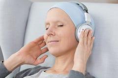 Cancer survivor listening to music. Cancer survivor in a blue headscarf, listening to music using big, wireless headphones Stock Image