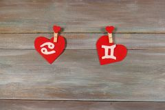 Cancer and twins. signs of the zodiac and heart. wooden backgrou. Nd. card. characters. Love. unusual handwork stock photography