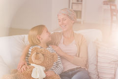 Cancer woman with positive attitude. Cancer women with positive attitude sitting on sofa with daughter stock photography