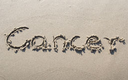 Cancer. Written on sand beach stock images