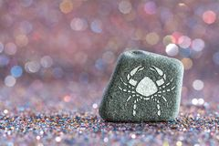 Cancer zodiac sign. A green stone with Cancer zodiac sign on glitter boke light background Royalty Free Stock Photo