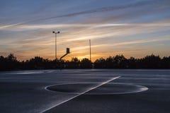 Cancha de básquet en puesta del sol después de la lluvia Cancha de básquet mojada del asfalto Foto de archivo