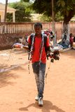 Unidentified local man carries some goods along the road in the. CANCHUNGO, GUINEA BISSAU - MAY 3, 2017: Unidentified local man carries some goods along the road stock photography