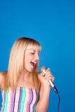 Canción femenina joven linda del canto, aislada sobre azul Fotografía de archivo