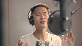 Canciones de registración del músico asiático joven en estudio almacen de metraje de vídeo