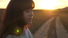 Canciones del canto de la mujer de negocios en la puesta del sol La muchacha feliz que viaja en una carretera nacional y canta en almacen de video