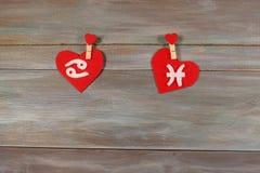 Cancro e pesce segni dello zodiaco e del cuore Backgroun di legno immagine stock