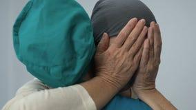 Cancro invecchiato turbato di sofferenza della donna che abbraccia infermiere, supporto avente bisogno paziente di morte video d archivio