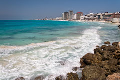 Cancun Beach Mexico. The turquoise waters of the Pacific Ocean in Cancun, Yucatan peninsula, Mexico, some stones and the hotel buildings on the shore stock photography