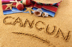 Cancun beach writing. The word Cancun written in sand on a Mexican beach, with sombrero, straw hat, traditional serape blanket, starfish and maracas Royalty Free Stock Photo