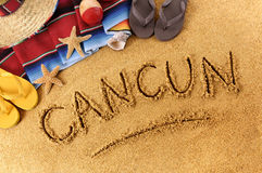 Cancun beach writing. The word Cancun written in sand on a Mexican beach, with sombrero, straw hat, traditional serape blanket, starfish and maracas Stock Image