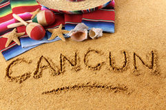 Cancun summer beach writing. The word Cancun written in sand on a Mexican beach, with sombrero, straw hat, traditional serape blanket, starfish and maracas Royalty Free Stock Images