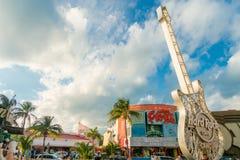 CANCUN MEXICO - JANUARI 10, 2018: Oidentifierat folk på det fria bredvid Hard Rock Cafe den metalliska gitarrstrukturen in Royaltyfri Foto