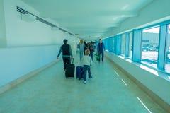 CANCUN MEXICO - JANUARI 10, 2018: Oidentifierat folk som går bära deras luggages i en korridor inom av Cancunen Royaltyfri Fotografi