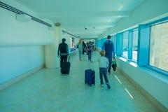 CANCUN MEXICO - JANUARI 10, 2018: Oidentifierat folk som går bära deras luggages i en korridor inom av Cancunen Royaltyfria Bilder