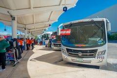 CANCUN MEXICO - JANUARI 10, 2018: Oidentifierat folk som går i flygplatsen, och några touristictbussar som parkeras på på Royaltyfri Bild