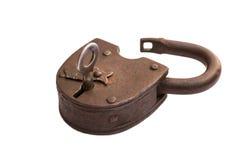 Candado abierto oxidado viejo aislado en el fondo blanco, llave en la cerradura fotos de archivo