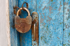 Candado cerrado viejo oxidado en puerta resistida de madera Foto de archivo libre de regalías