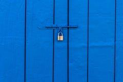 Candado de cobre amarillo viejo en la puerta azul de madera Imagen de archivo libre de regalías