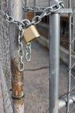 Candado del oro en la cerca de Chainlink Foto de archivo libre de regalías