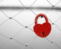 Candado en forma de corazón rojo del amor en una cerca del puente. Foto de archivo