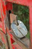 Candado en una puerta roja de la granja del metal Foto de archivo