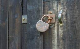 Candado oxidado viejo en la puerta de madera Foto de archivo libre de regalías