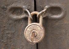 Candado oxidado viejo en un primer de la puerta del hierro imagenes de archivo