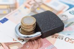 Candado que mantiene el dinero seguro Imágenes de archivo libres de regalías